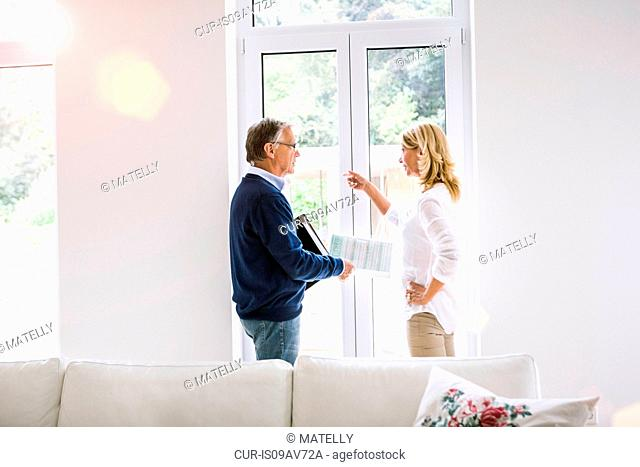 Couple in front of french doors discussing paperwork