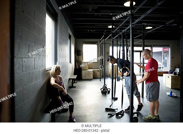 Personal trainer guiding man gymnastics rings gym
