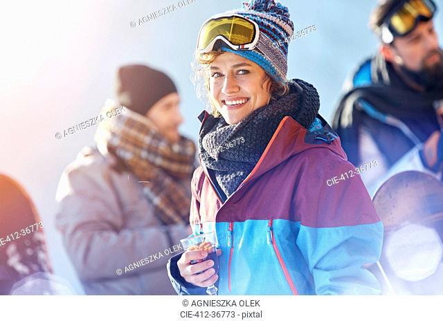 Portrait smiling female skier drinking cocktail