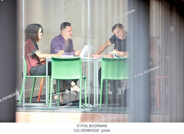 Design team brainstorming at design studio boardroom table