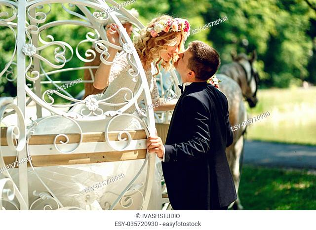 Romantic fairy-tale wedding couple bride and groom kissing in magical cinderella white carriage
