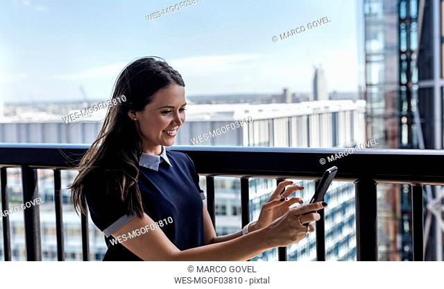 UK, London, smiling woman using cell phone on a roof terrace