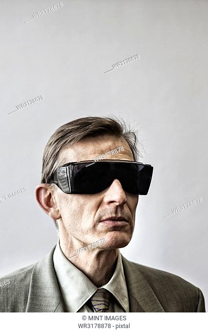 Studio portrait of Caucasian man actor wearing large sunglasses or protective eyeglasses with darkened lenses