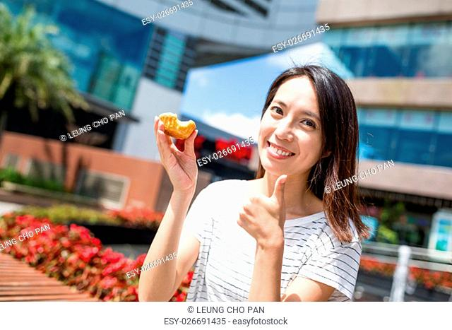 Woman enjoy egg tart in Hong Kong city