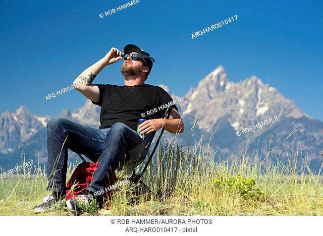 Man sitting in camp chair and watching solar eclipse with Teton Mountains in background, Jackson Hole, Wyoming, USA