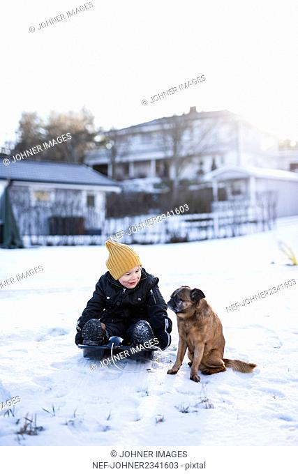 Boy sitting in snow with dog