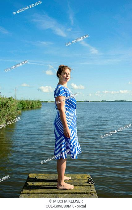 Woman posing in the Frisian lake district in vintage dress, Sneek, Friesland, Netherlands
