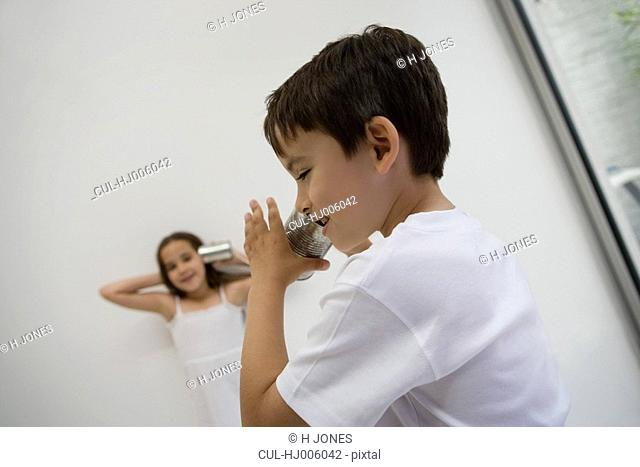 Girl and Boy using a tin can as a phone