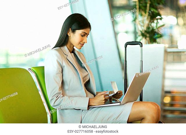 pretty indian businesswoman checking flight information on laptop computer at airport