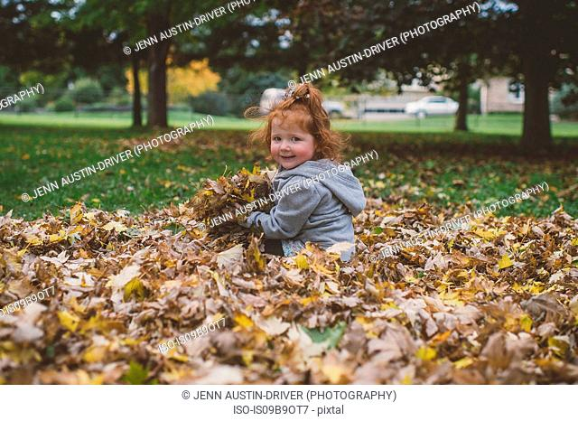 Portrait of red haired female toddler in park with bundles of autumn leaves