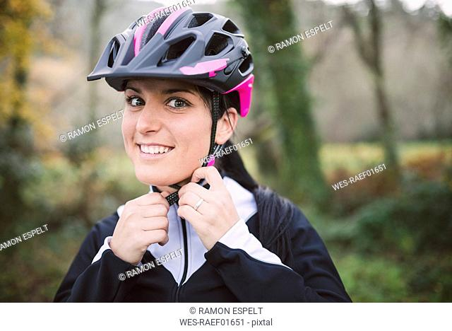 Portrait of smiling woman putting on bicycle helmet