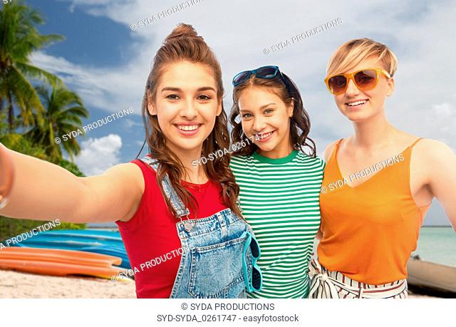 happy female friends in sunglasses taking selfie