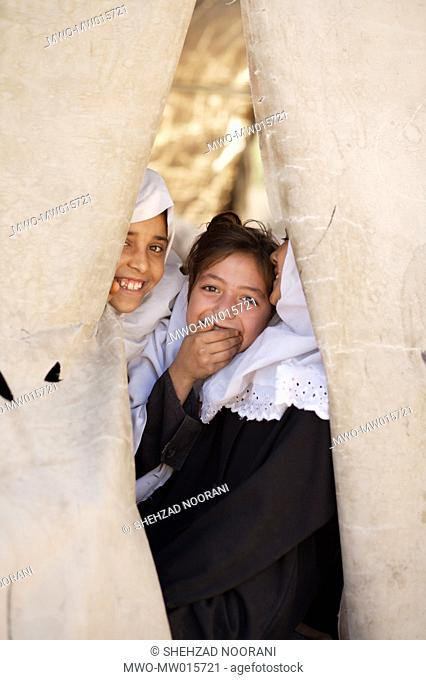 Afghan girls smile at the camera from their tent classroom at Phool-e-Rangeena Government School in the north-western city of Herat Like many schools throughout...