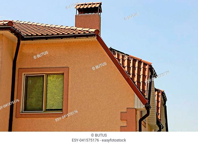 part of a private large brown house with a window under a roof against the sky