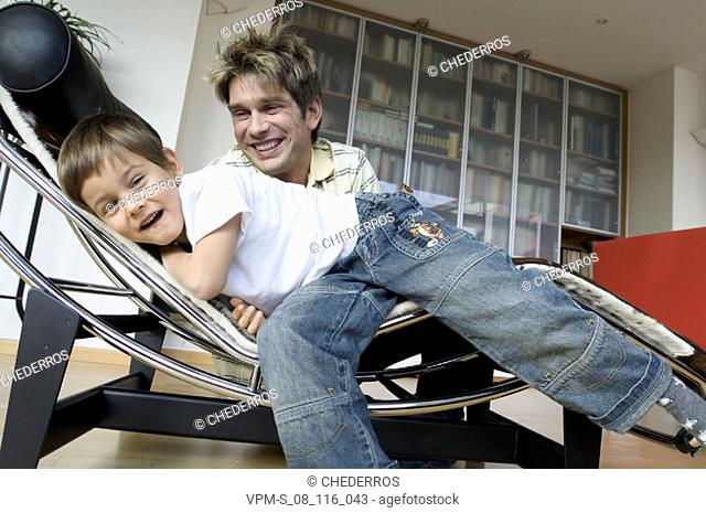 Portrait of a son lying on a chaise longue with his father smiling