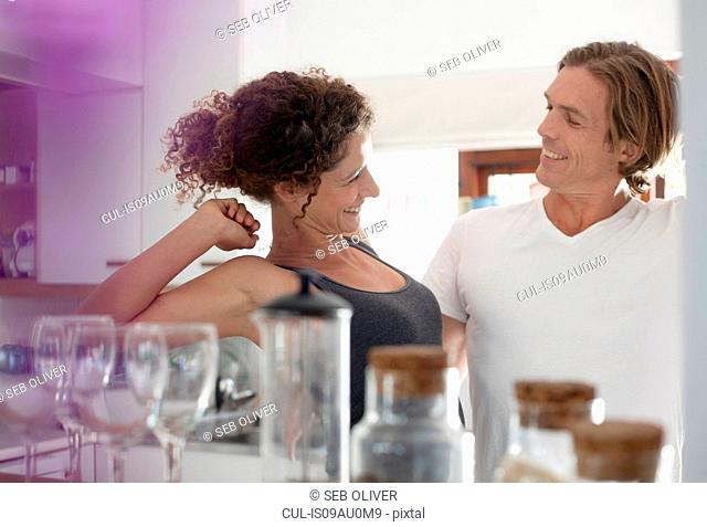 Couple in sleepwear, in kitchen, stretching, smiling