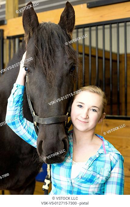 Teenage girl cleaning horse hoof