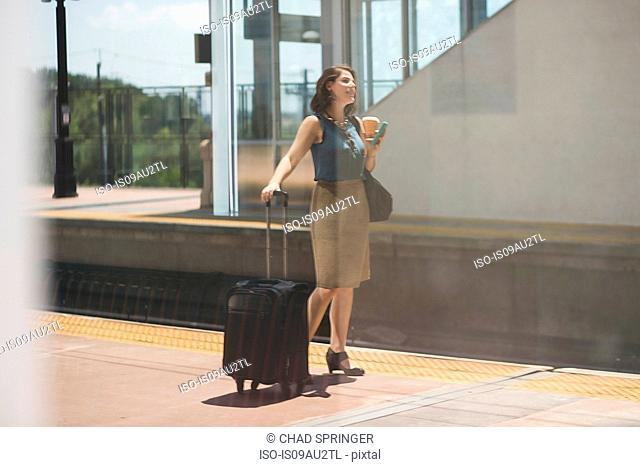 Mid adult woman waiting at train station, holding wheeled suitcase and coffee cup