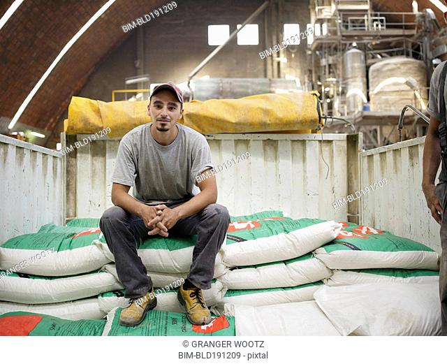 Hispanic worker sitting on bag in factory