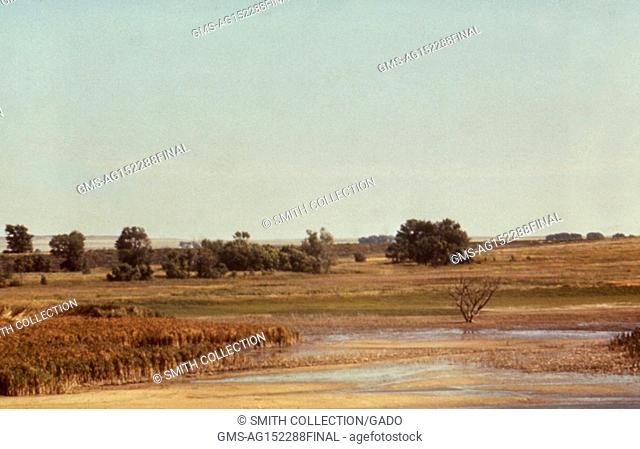 Landscape photograph of the edge of a lake reservoir set in a flat, grassy area, with trees and distant hills visible, Julesburg Reservoir, Colorado, 1976