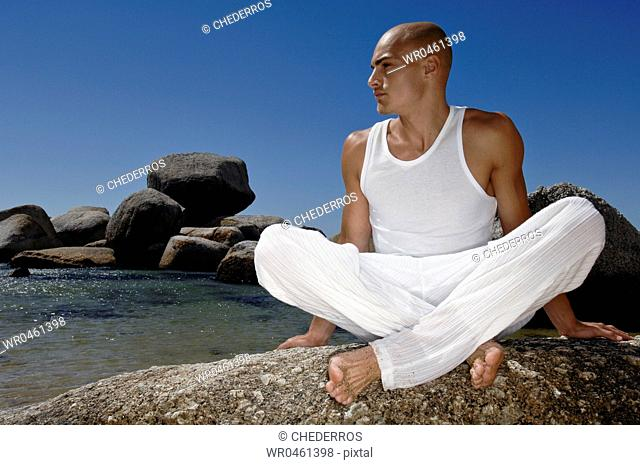 Young man sitting on a boulder