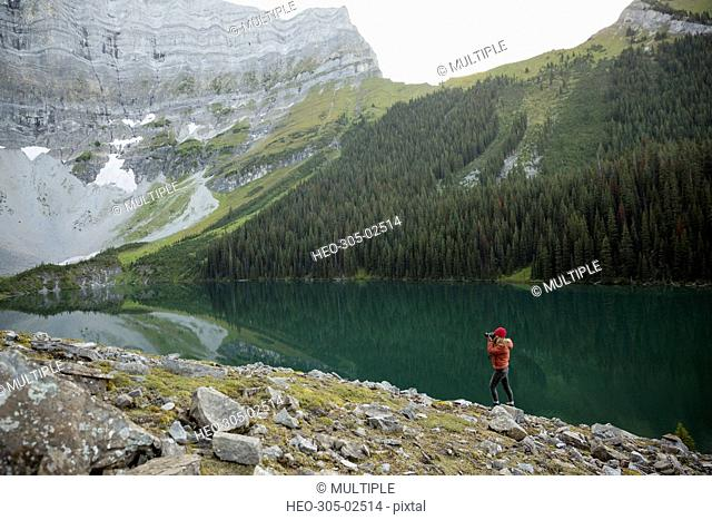 Female photographer photographing remote mountain lake view