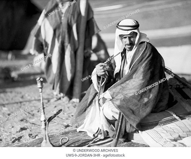 Jordan: c. 1926.Bedouin Sheik Muthgal Pasha seated by his tent and smoking while camping near Madaba