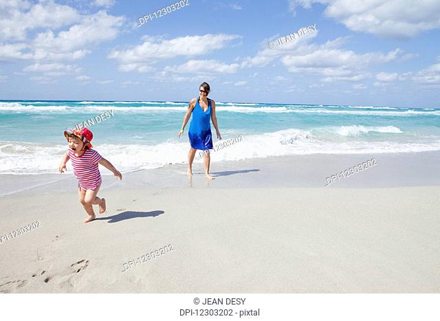 Child running and crying on the beach with her mother; Varadero, Cuba