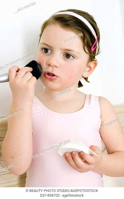 Girl applying make up with a brush