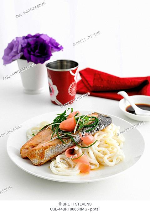 Plate of fish and pasta on table