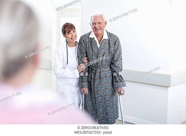 Doctor leading elderly patient with crutches on hospital floor