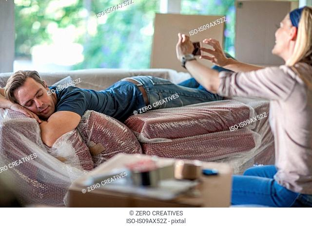 Moving house: man sleeping on bubbled wrapped sofa, woman taking photograph of him, using smartphone