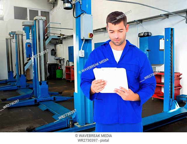 Automobile mechanic holding clipboard