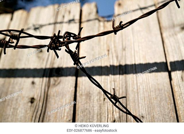 barbed wire on a wooden fence