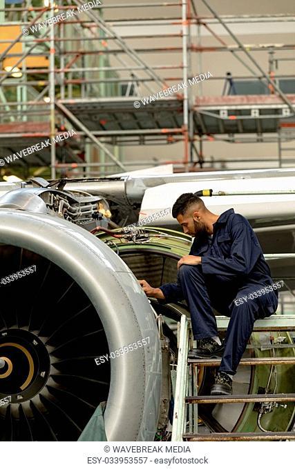 Aircraft maintenance engineer examining turbine engine of aircraft