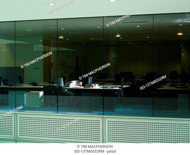 A man sleeps at his desk
