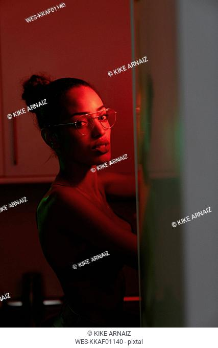 Portrait of beautiful young woman wearing bra and glasses in a dark illuminated room