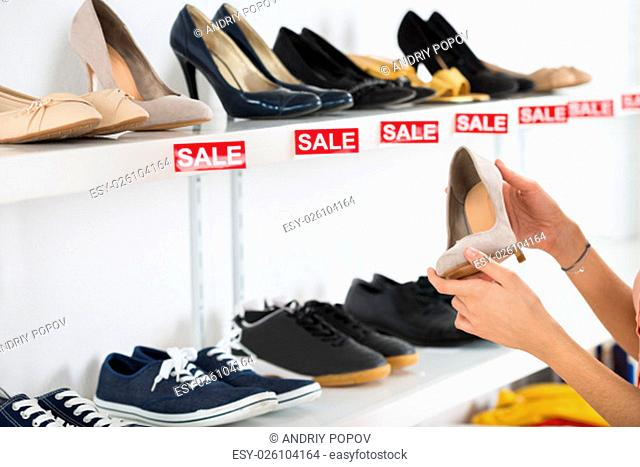 Cropped image of young woman buying shoe in retail store
