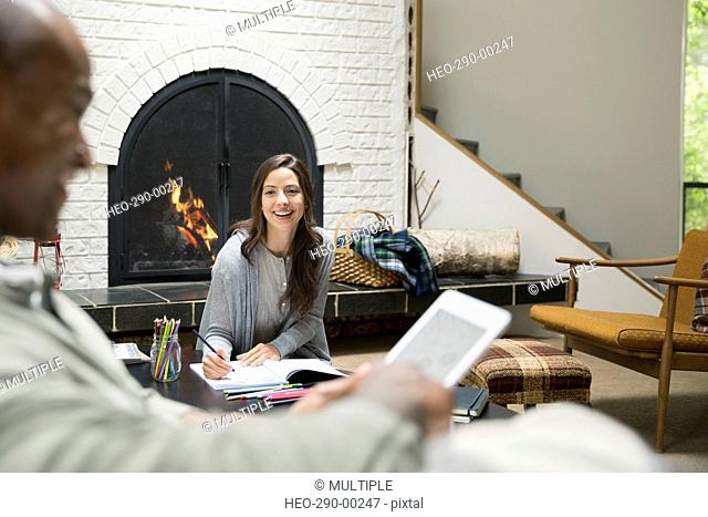 Smiling couple reading and writing in living room near fireplace