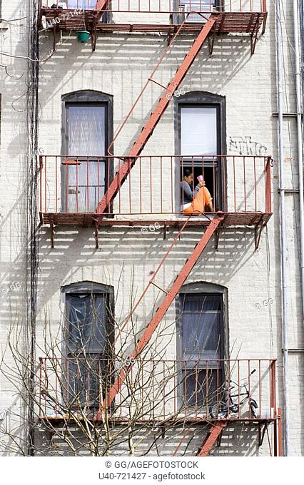 Woman sitting on fire escape, NYC, USA
