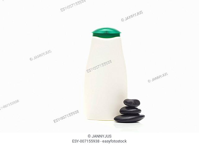 cosmetic containers and spa black stones isolated on white