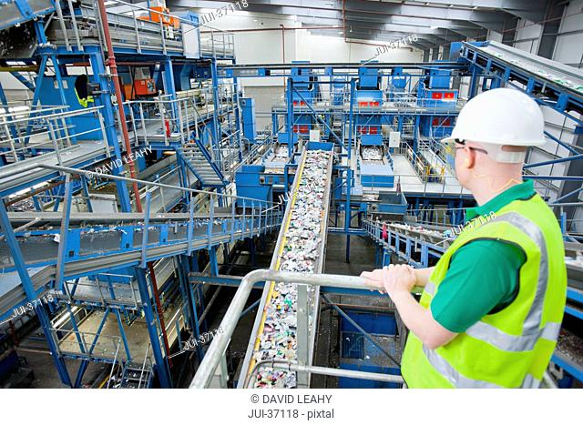 Worker watching plastic on conveyor belt in recycling plant
