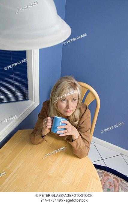 Middle-age blond woman drinking coffee in her kitchen