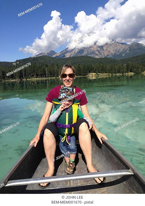 Mother and son sitting in canoe on still lake