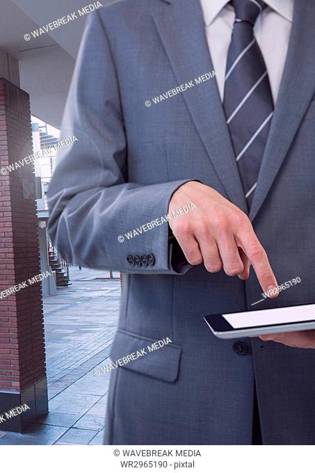 Businessman holding tablet on public street