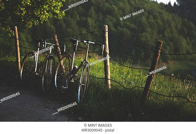 Two bicycles leaning against a rickety fence in the countryside
