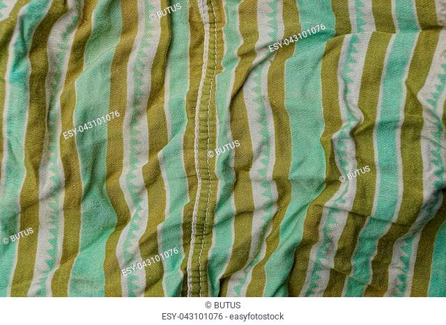green brown fabric background from a piece of crumpled clothes