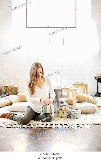 A woman sitting on the ground by a stack of parcels, opening presents