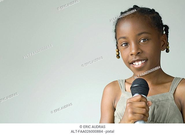 Little girl holding microphone, smiling at camera, portrait