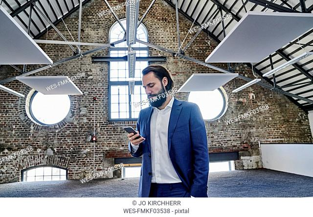 Businessman using cell phone in a loft